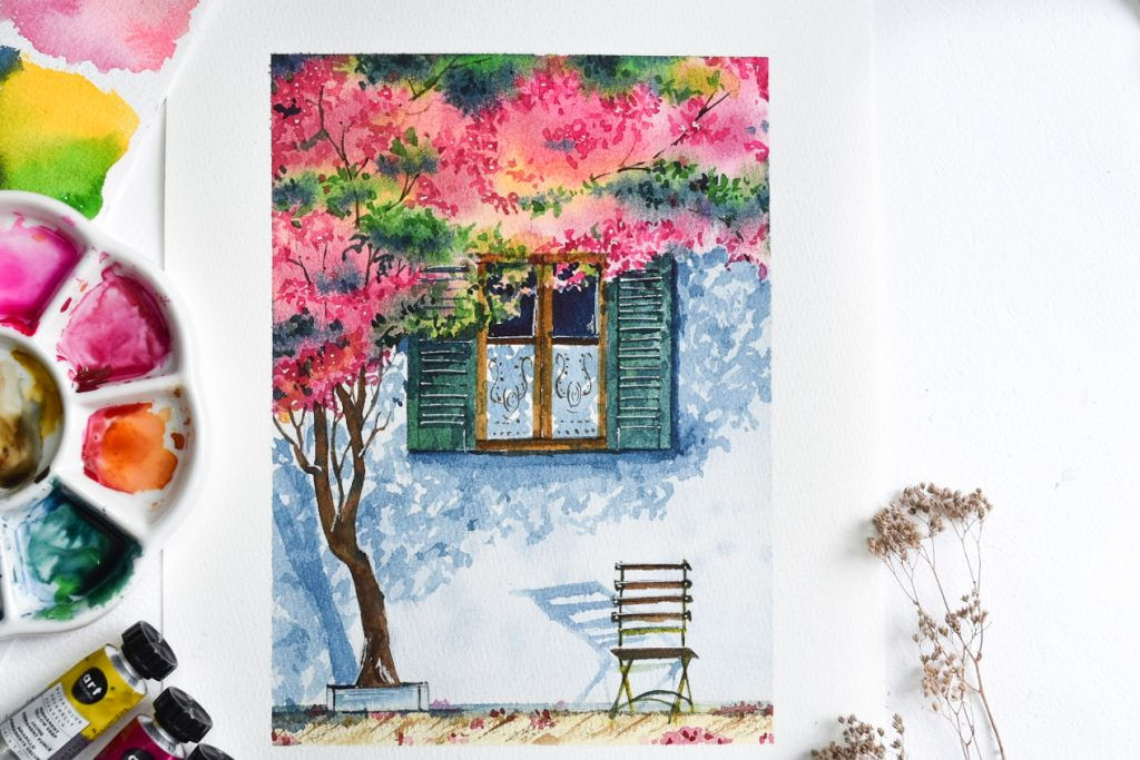 wooden chair under a window with green shutters under the shade of a tree with pink and green leaves.