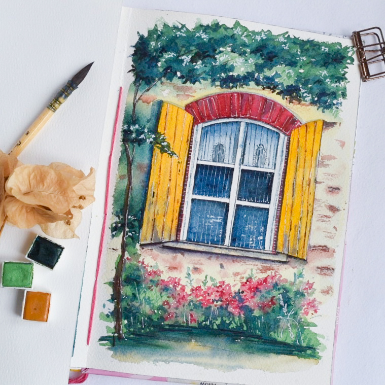 image of watercolor painting of a window of with yellow shutters with pink flowers underneath. on the left is three watercolor pans in green, med yellow and dark green.
