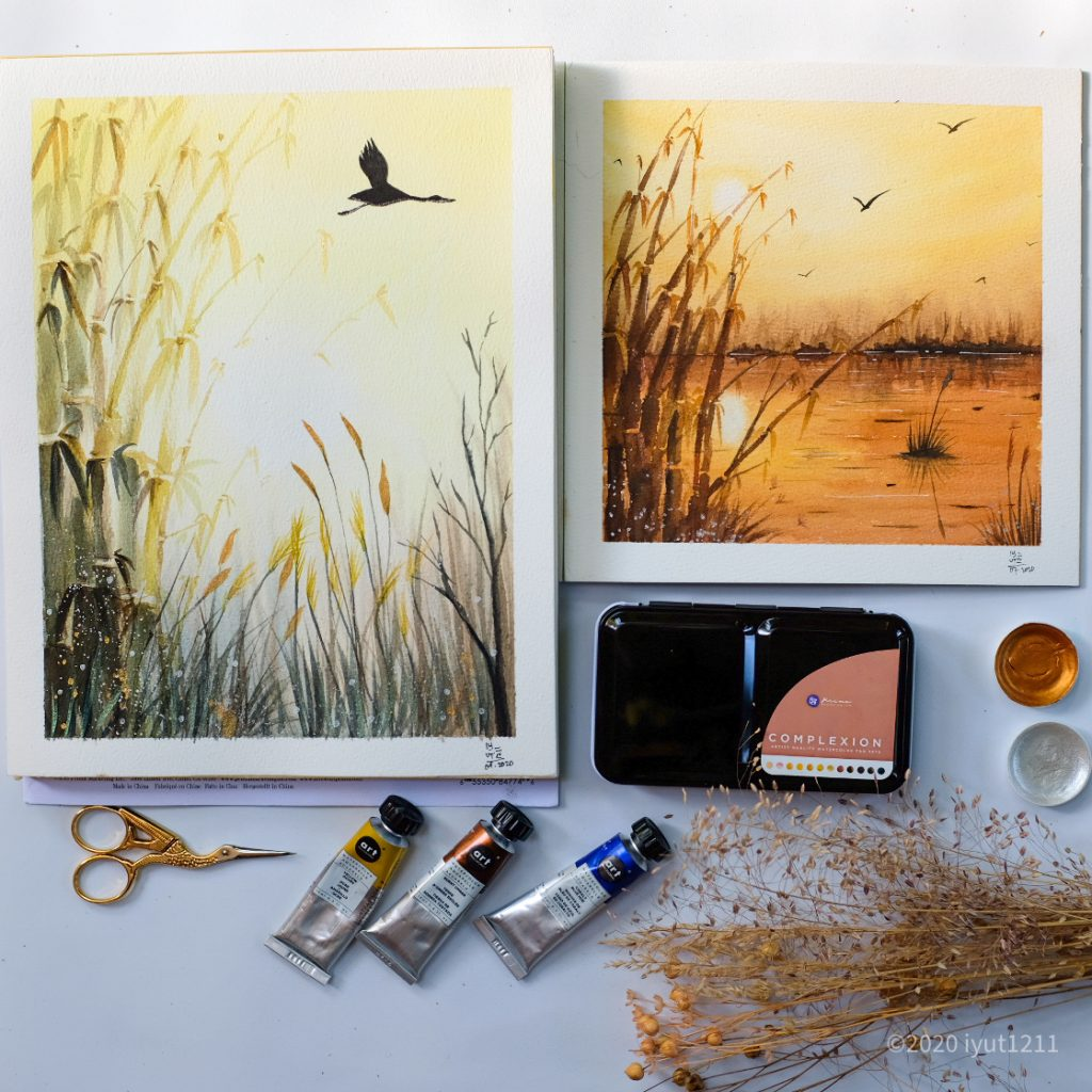 two nature water color paintings. at the bottom of the image is small sewing  scissors,, three watercolor paint tubes in red, blue and yellow, a closed confection pallet in complexion, to pots of metallic accents and decorative wheat.