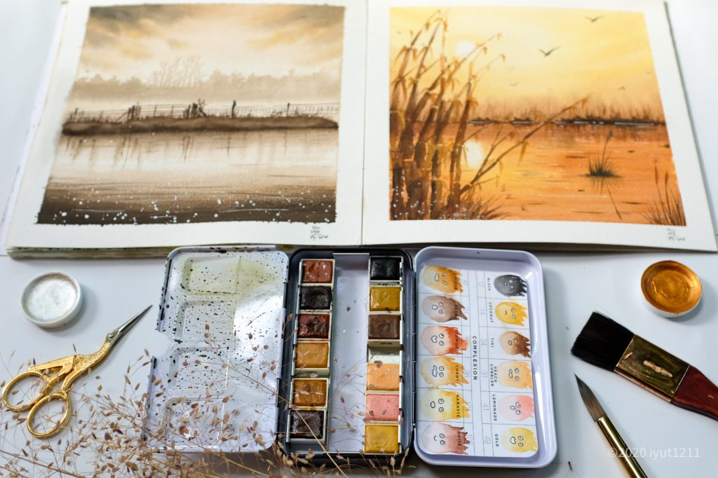 two nature watercolor paintings. at the bottom of the image is small sewing scissors, an open confection pallet in complexion, to pots of metallic accents and decorative wheat and paint brushes in the right hand corner