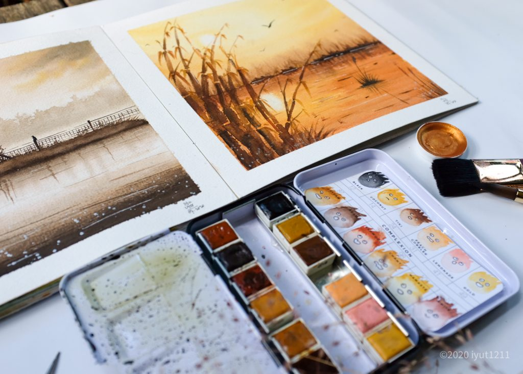 two nature watercolor paintings. at the bottom of the image is an open confection pallet in complexion, a pots of metallic accents and paint brushes in the right hand corner