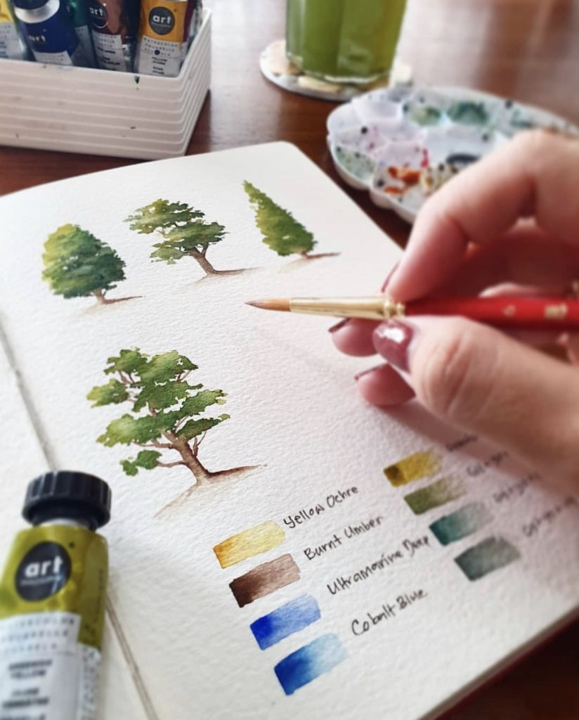 watercolor trees in a sketchbook with swatches underneath of burnt umber, yellow, ultramarine, and colbolt blue