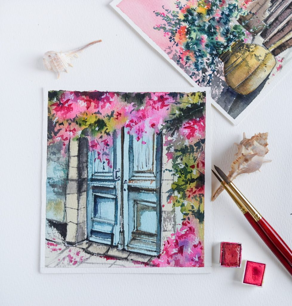image of double blue door, surrounded by pink blossoms. two watercolor pans and a paintbrush resting on a seashell.