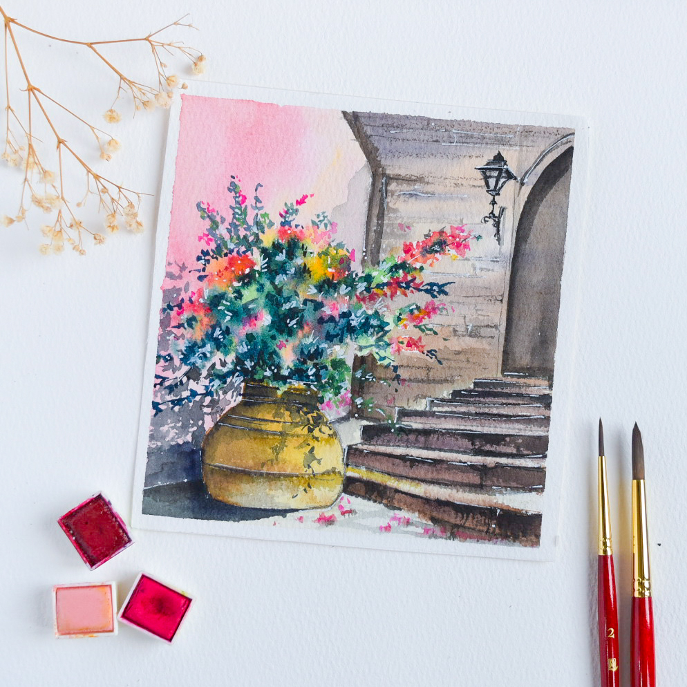 image of a watercolor painting featuring a plant in a gold pot at the foor of stone steps. on to the right are two paint brushes and on the left is three watercolor pans in pin, hot pink and red.